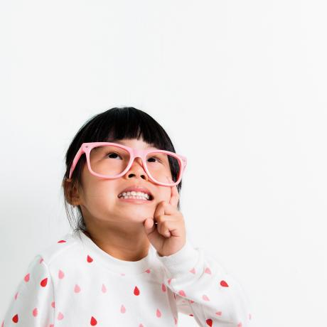 cute little girl in pink glasses and white shirt with hearts looking up
