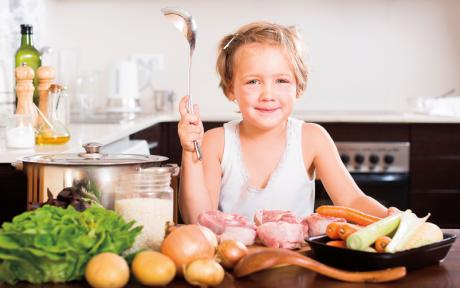 little girl sitting at a counter full of vegetables holding a ladle and smiling