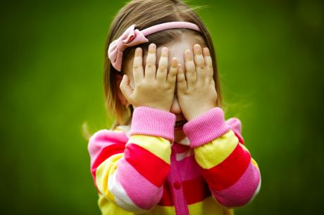 little girl in colourful striped sweater covering her eyes