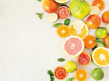 assortment of citrus fruits cut open and arranged in a crescent shape