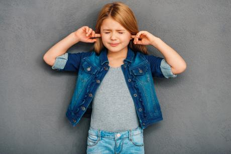 young girl plugging her ears and shutting her eyes
