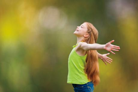 young girl with long red hair, looking upward, throwing her arms back and smiling