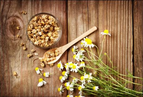 chamomile flowers with dried herbs in a bowl and spoon on a wooden background