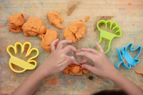 child's hands playing with play dough