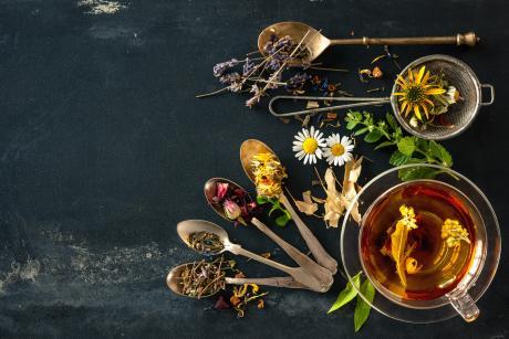 assorted herbs and spoons on a black background