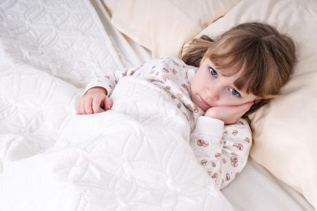 child lying in bed looking distressed