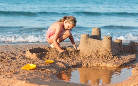 young girl building a sand castle on the beach with water behind her