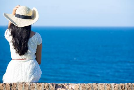 woman with long dark hair and a white sun hat sitting looking at the water