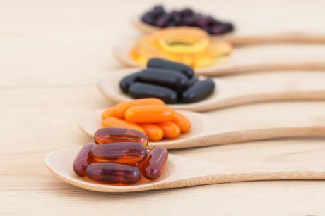 wooden spoons lined up and filled with various vitamins