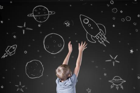 young child observing chalkboard drawings of space