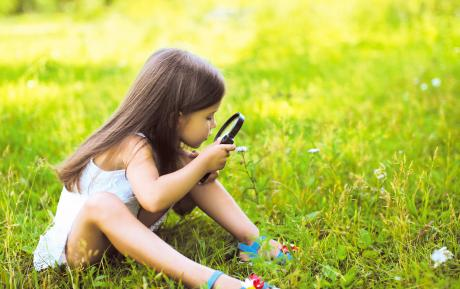 small girl sitting in the grass with a magnifying glass