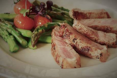 roasted meat, asparagus and tomatoes on a plate