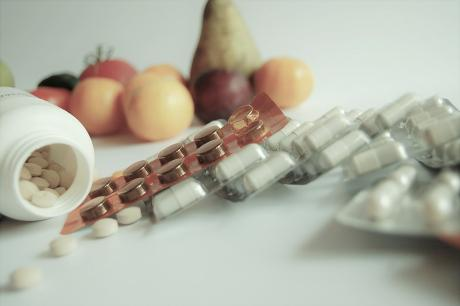 vitamin supplements with fruit in the background