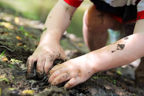 small child playing in the mud