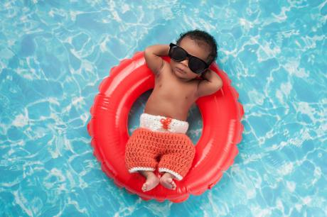 infant floating on an inflatable toy in the pool