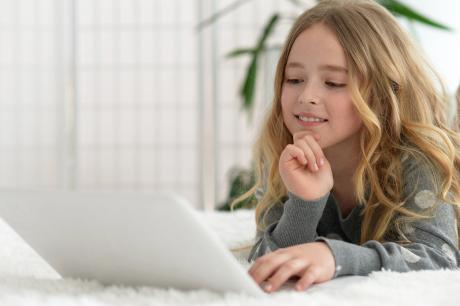 tween girl looking at her laptop