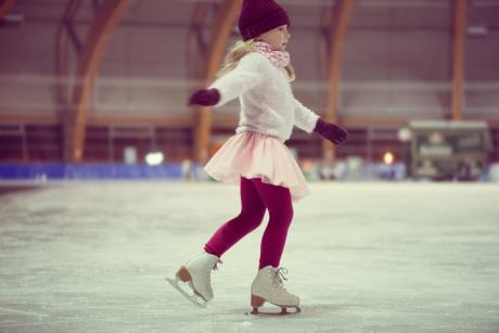 little girl skating in a red cap, warm gloves and sweater