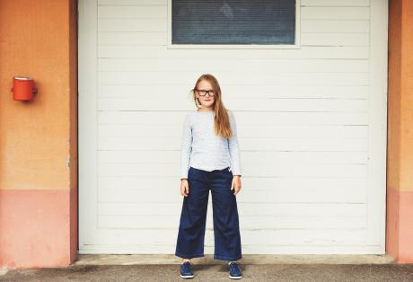 pre-adolescent girl standing in front of garage door wearing blue top, denim culottes and eyeglasses