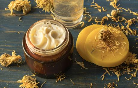 Facial cream of calendula and beeswax, on a blue wooden background