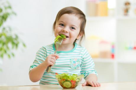 young child eating a healthy salad