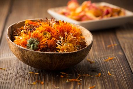 Dried yellow flower buds from the herb calendula. The dried flowers are in a small bowl.