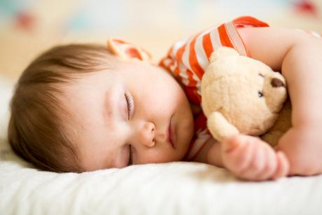A toddler sleeping on his side and hugging a teddy bear