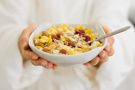 A white cereal bowl with corn flakes and berries