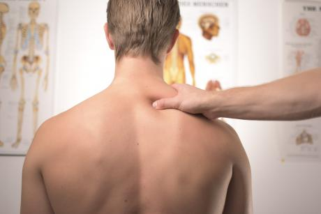 A chiropractor places a hand on the shoulder of a man