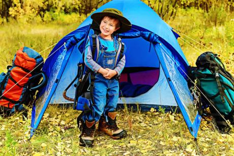 young boy standing in front of small blue tent