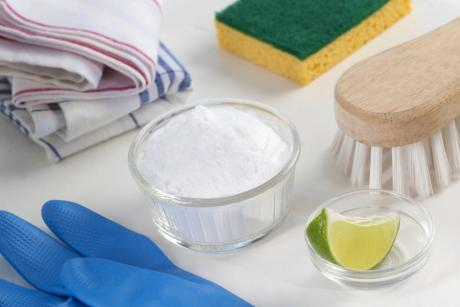 cleaning tools, rubber gloves, rags, lime and baking soda in a bowl