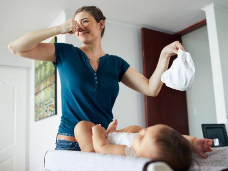 woman changing baby's diaper and plugging her nose