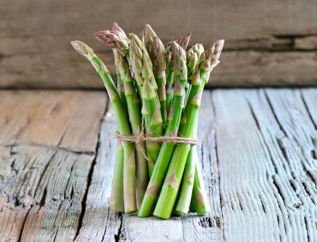 bunch of asparagus tied with string on wooden tabel