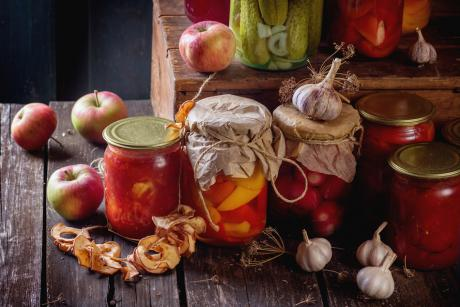 many homemade glass jars with preserved food (cucumbers, tomatoes, peppers), with garlic and fresh and dried apples over old wooden table