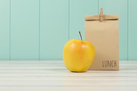 brown bag lunch and yellow apple