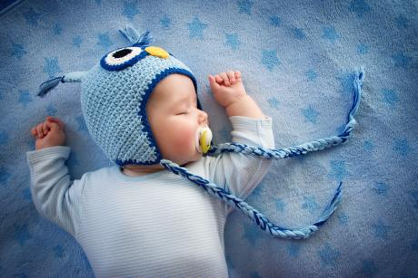 infant sleeping on back with soother and wearing a blue knitted hat