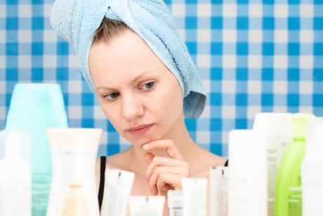 woman with towel on her hear looking pensively at skincare products